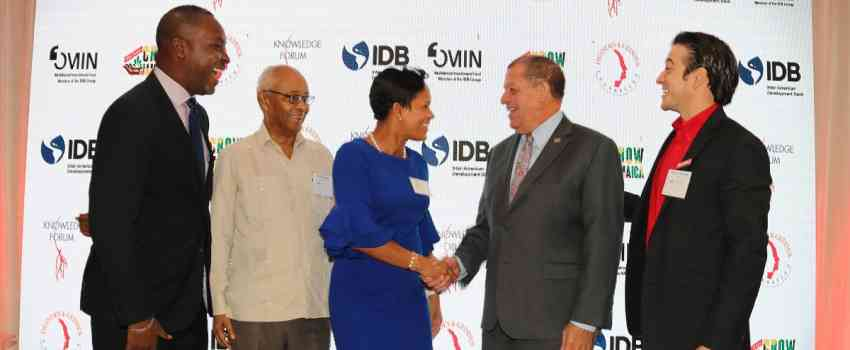 Minister Shaw greets Gillian Hyde of the Jamaica National Group at Red Stripe's Knowledge Forum
